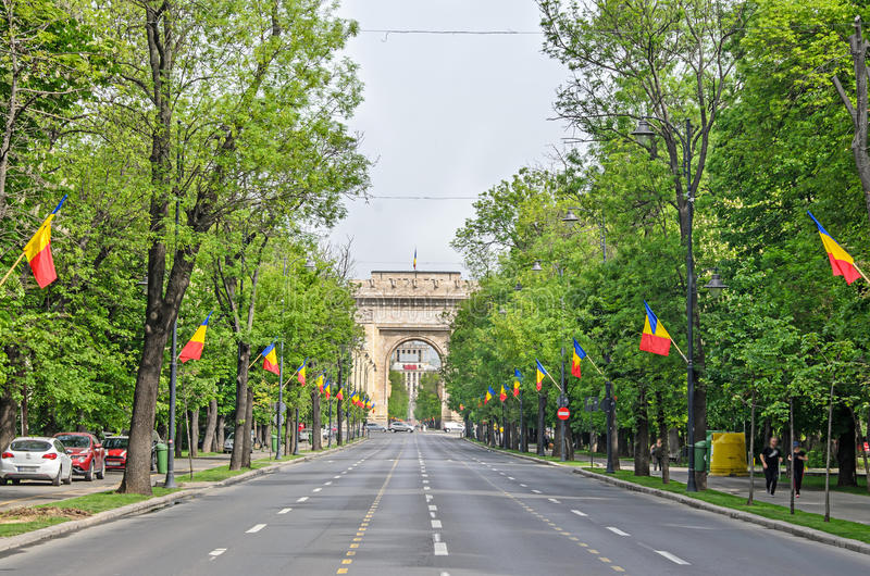 The Arch of Triumph Arcul de Triumf from Bucharest Romania. International Day with romanian flags, view from Kisseleff Avenue royalty free stock image