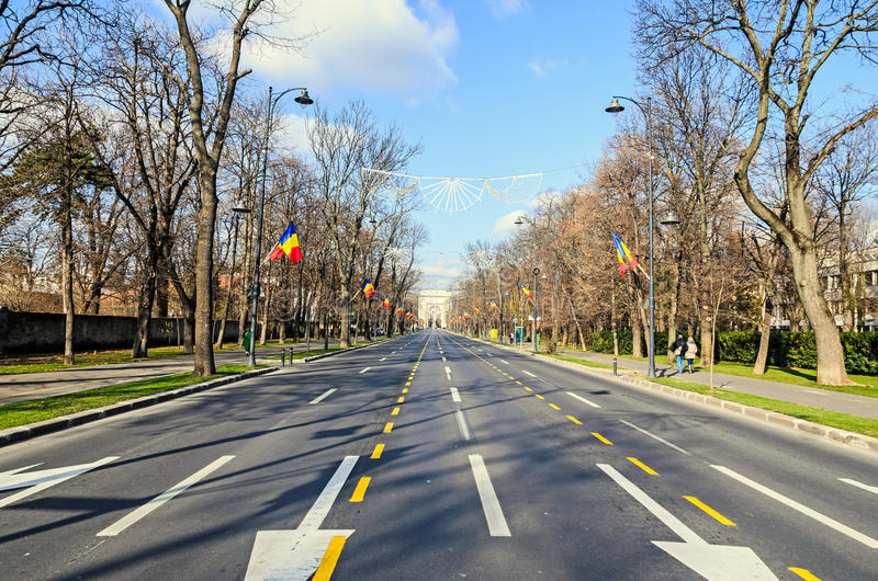 The Arch of Triumph Arcul de Triumf from Bucharest Romania. National Day with romanian flags, view from Kisseleff Avenue royalty free stock photos