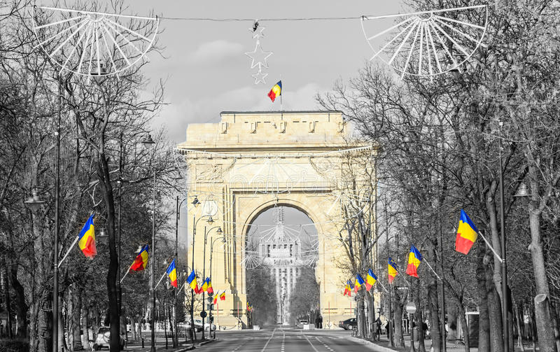 The Arch of Triumph Arcul de Triumf from Bucharest Romania, National day. With romanian flags, view from Kisseleff Avenue royalty free stock photo