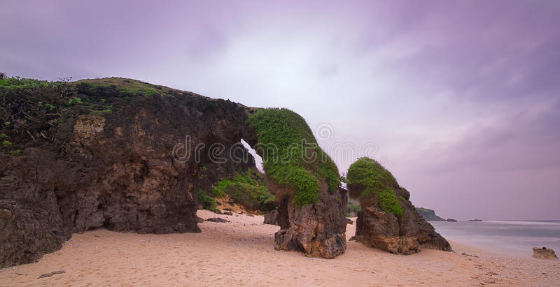 Arch of Violet Skies. The hidden arch of Sabtang island under a violet sky stock image