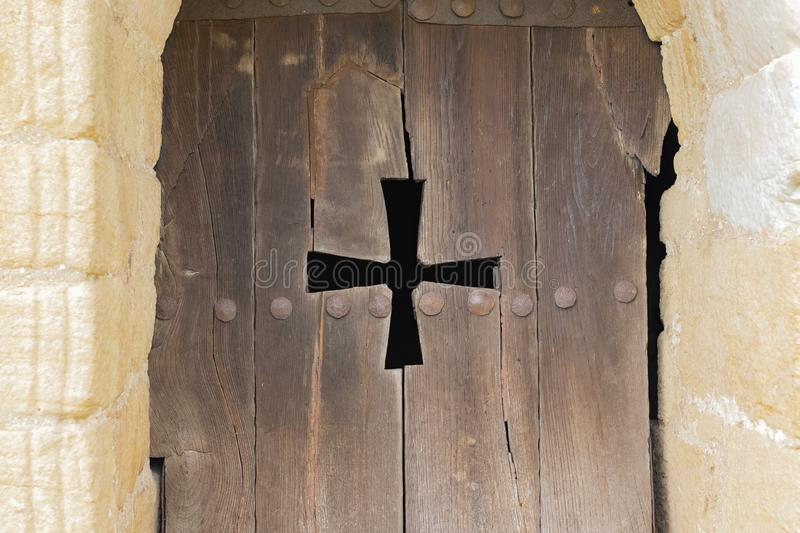 Arch window of a catholic church with wooden shutters and a carved cross. The window of the Catholic Church in the form of an arch with wooden shutters and stock images