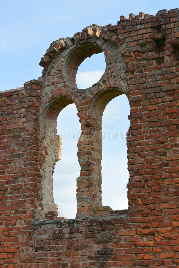 Arch window on ruined red brick wall in an ancient castle. Arch window on ruined red brick wall in an ancient castle on blue sky background royalty free stock photos
