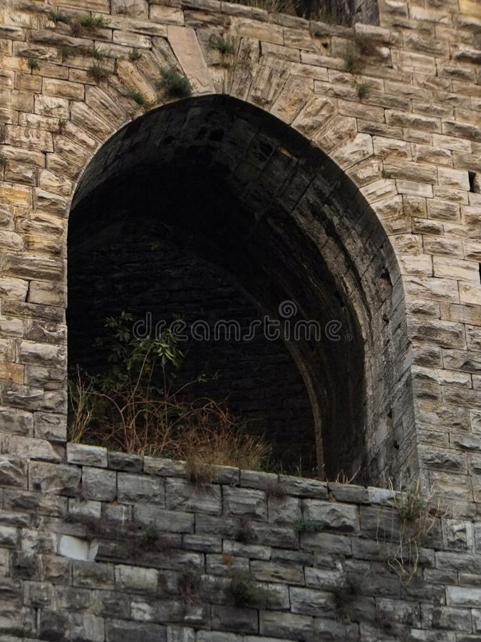 An arch window in a tower of the stone city wall in Como, Italy. Partly bathed in soft reflection of the light of the setting sun.  royalty free stock images