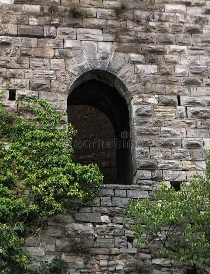 An arch window in a tower of the stone city wall in Como, Italy. Young trees reaching up to it with their foliage.  royalty free stock image