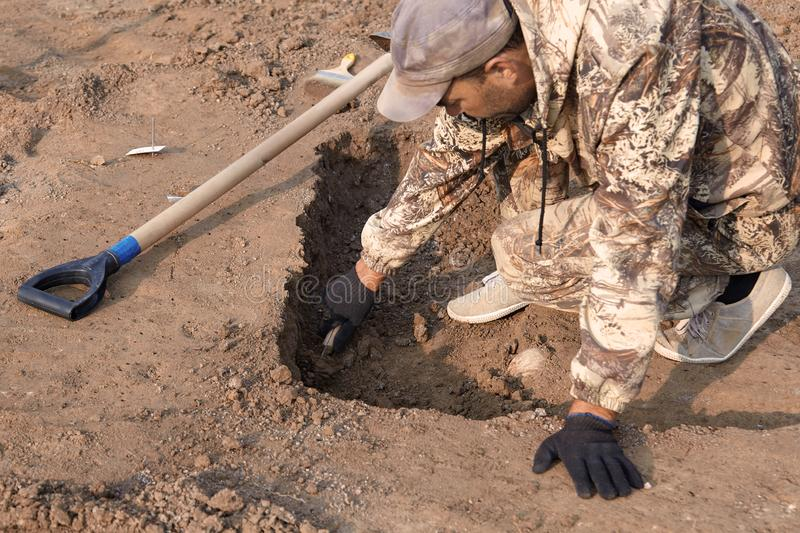 Archaeological excavations. The archaeologist in a digger process. Hands with knife conducting research on the ground, shovel is n. Ear. Outdoors, copy space stock photo