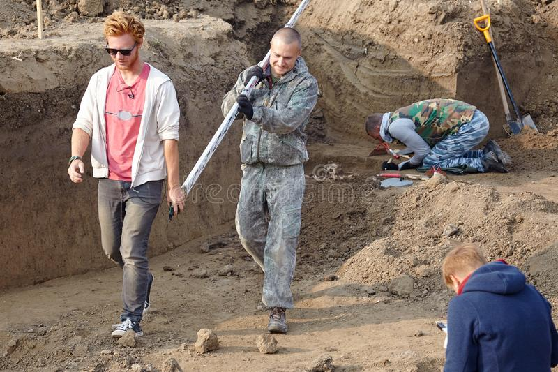 Archaeological excavations. The archaeologists in a digger process, researching the tomb with human bones, going with measure plan royalty free stock image