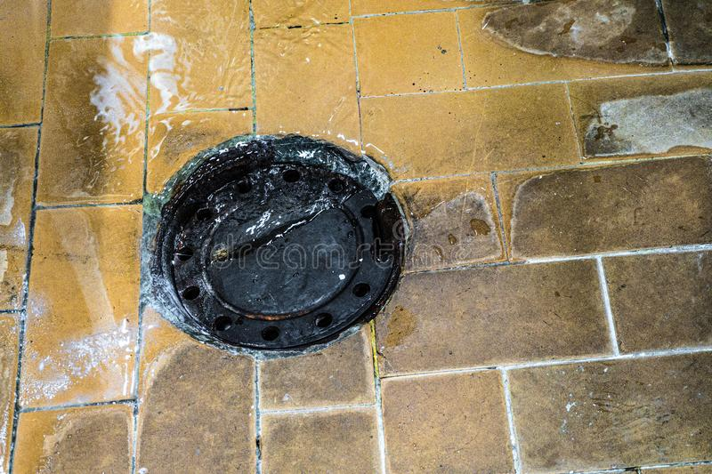 Archaic old tiled floor with drain in an industrial plant.  stock photo