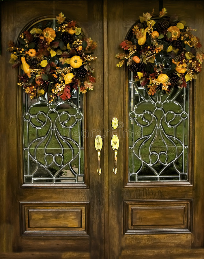 Arched Beveled front doors with Fall Wreths. Inviting entry with double beveled doors and a fall wreath royalty free stock photography