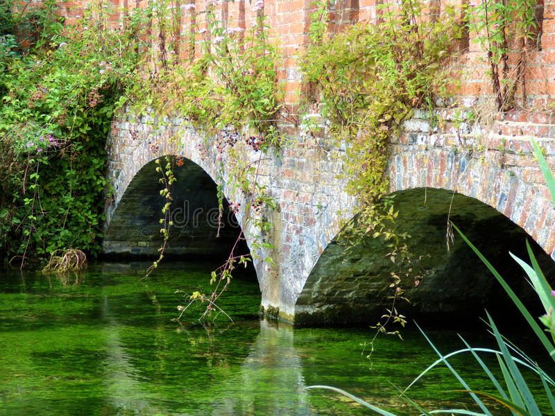 Arched bridge. Over river flowing on a summers day in English village royalty free stock photos