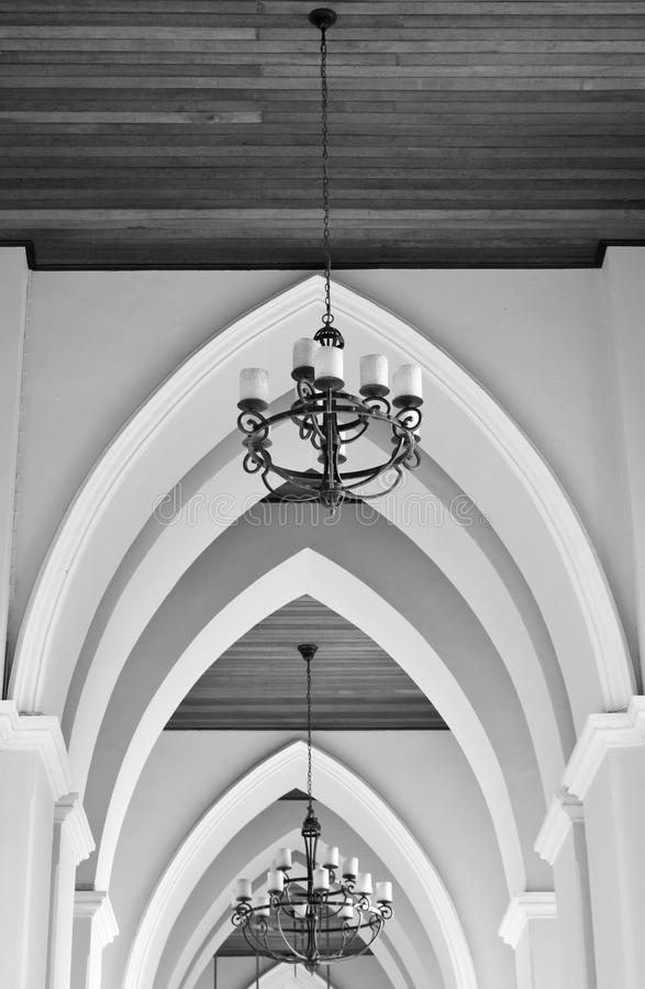 Arched ceiling of church with chandelier. In black and white royalty free stock photo