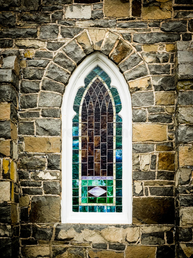 Arched Stained Glass Window in Stone Wall. Arched, stained glass window in the stone wall of a church building stock photography