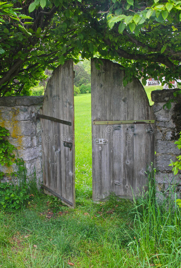 Arched garden door, framed with beech hedge royalty free stock image