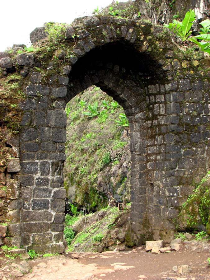 Arched Gate. An old arched gate made of black stones in a ruined fort in India stock photo