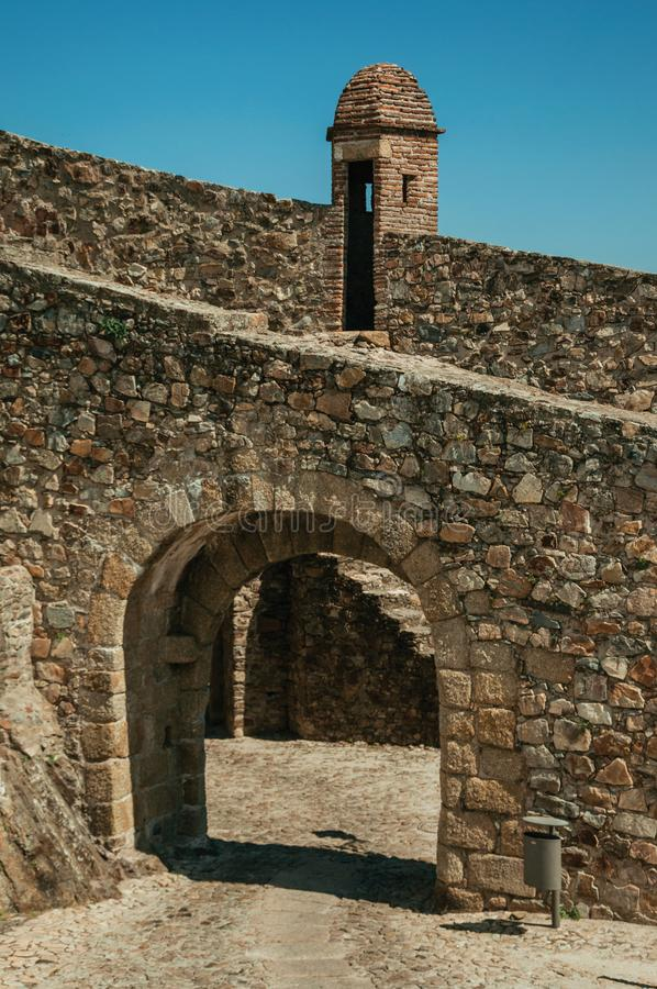 Arched gateway in the city outer wall made of rough stone. Arched gateway in the city outer wall made of stone with pathway under it and watchtower, on sunny day royalty free stock images