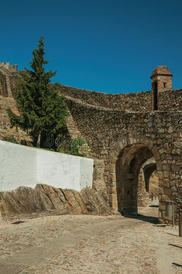 Arched gateway in the city outer wall made of stone. With pathway under it and watchtower, on sunny day at Marvao. An amazing medieval fortified village perched royalty free stock image