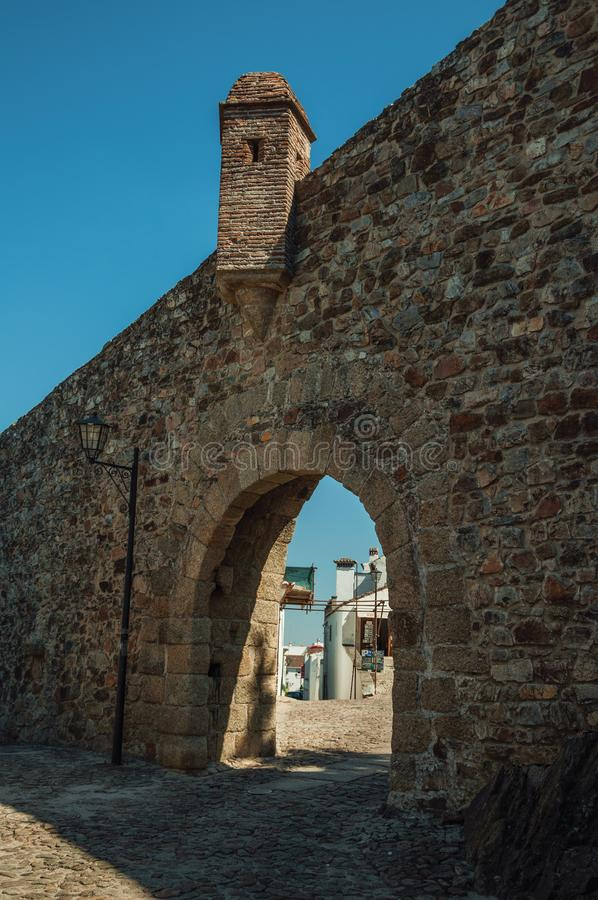 Arched gateway in the stone outer wall of Marvao. Arched gateway in the outer wall made of rough stone with pathway and watchtower, in a sunny day at Marvao. An stock photos