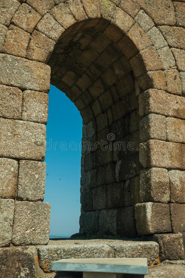 Arched gateway on stone wall over rocky hill stock photos