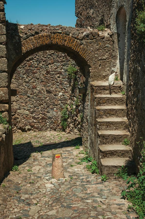 Arched gateway in stone wall with staircase. Cobblestone pathway going to arched gateway in stone wall with staircase, on a sunny day at Castelo de Vide. Nice royalty free stock photography