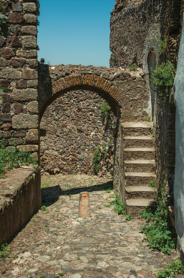 Arched gateway in stone wall with staircase. Cobblestone pathway going to arched gateway in stone wall with staircase, on a sunny day at Castelo de Vide. Nice stock photography