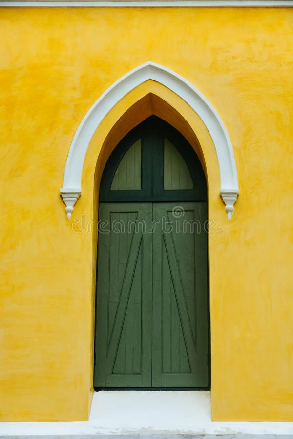 An arched green wooden door decorate with white stucco arch on the top in the yellow fresco plaster cement wall finishing stock images