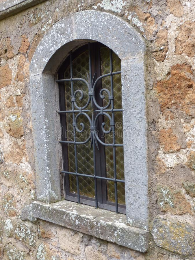 An arched medieval window with stone trim. Arched medieval window stone trim wrought iron wall house rock  architecture design italy tuscan stock photo