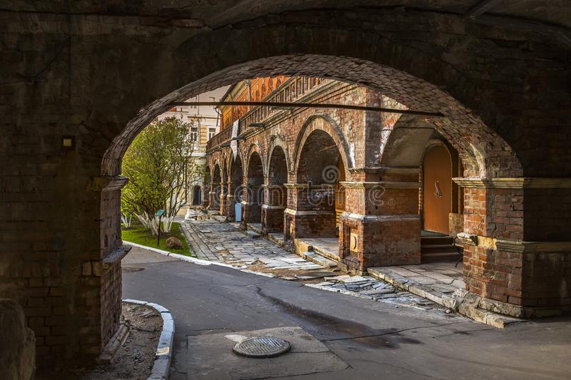 Arched passage to the courtyard and the old brick colonnade stock photo
