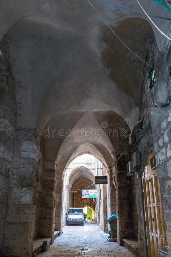 Arched passage under the houses on Derech Shaar HaArayot street inside the old city of Jerusalem leading from the Lion Gate in Isr royalty free stock photography