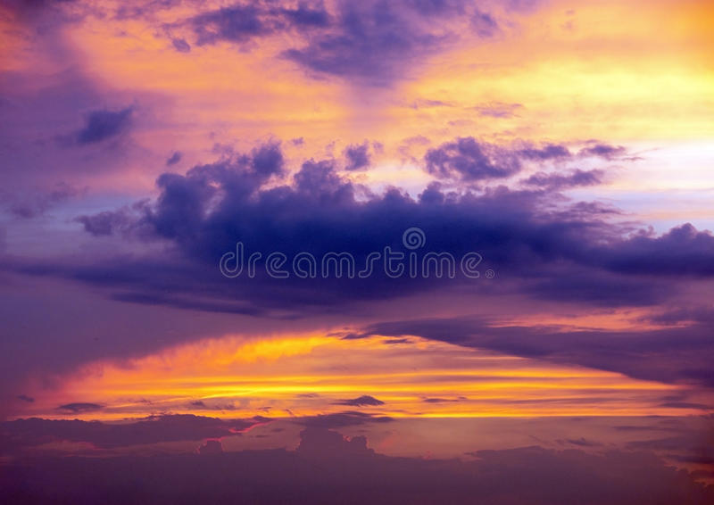 Arched purple cloud in sunset sky royalty free stock image