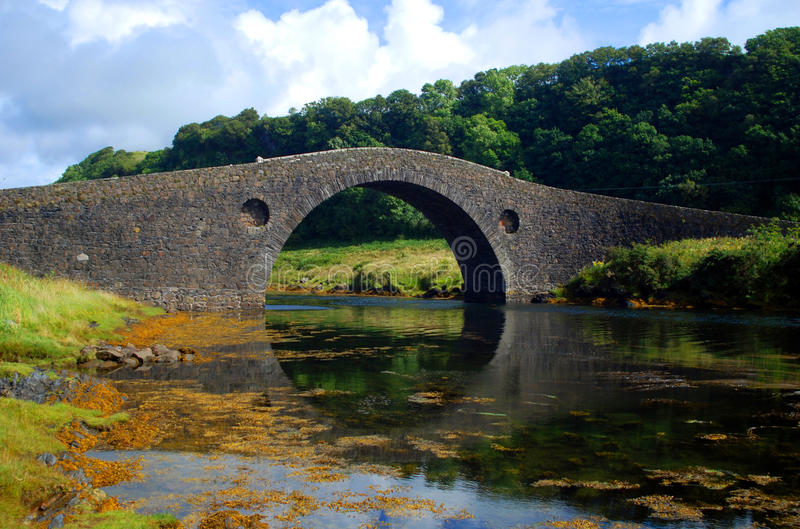 Arched stone bridge. An old stone bridge built in an arch over water stock photos