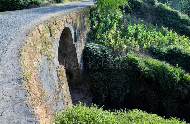 Arched stone bridge under cobblestone road. Arched stone bridge under a cobblestone road traverses a dry river bed on the town of Ribeira Filipe on the island of stock photos