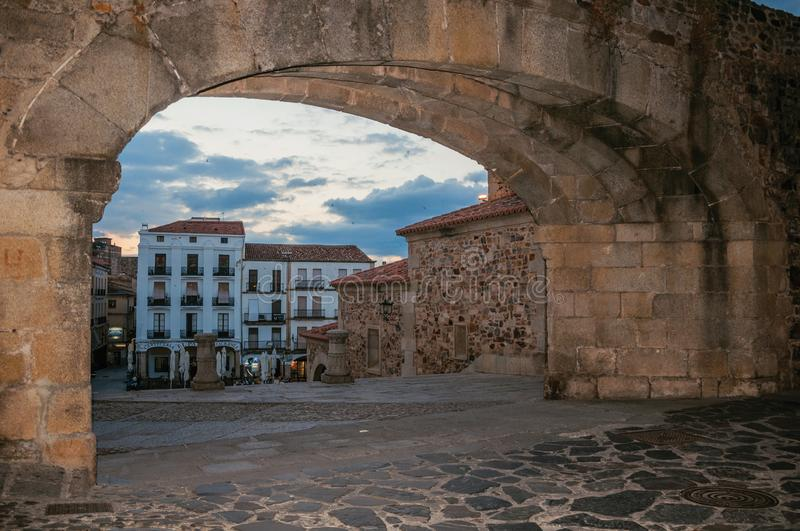 Arched stone gateway and old buildings at dusk in Caceres royalty free stock photos