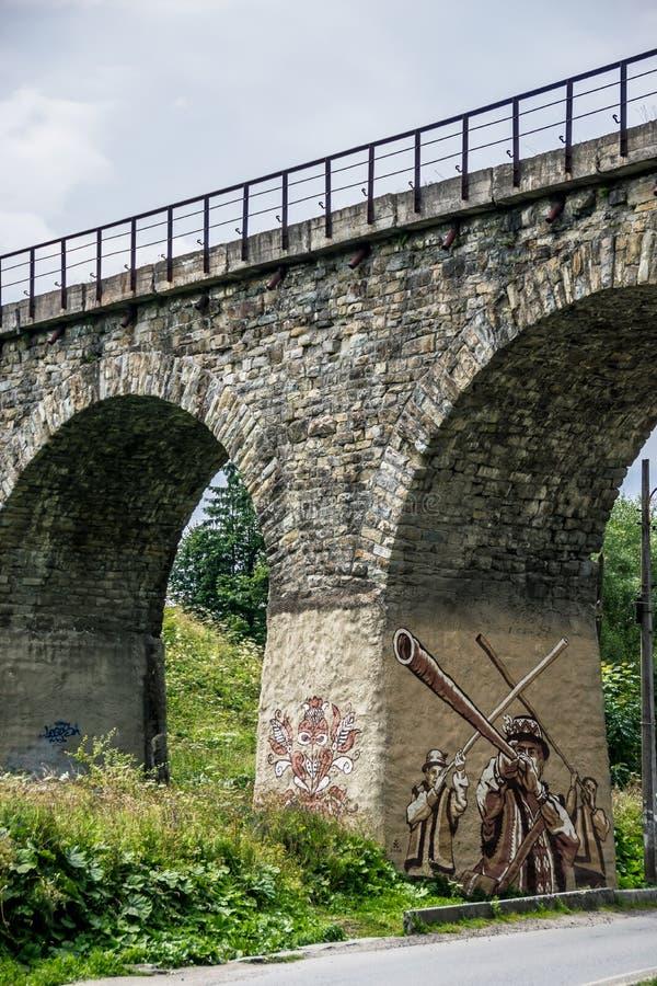Arched stone railway bridge with street art stock photos