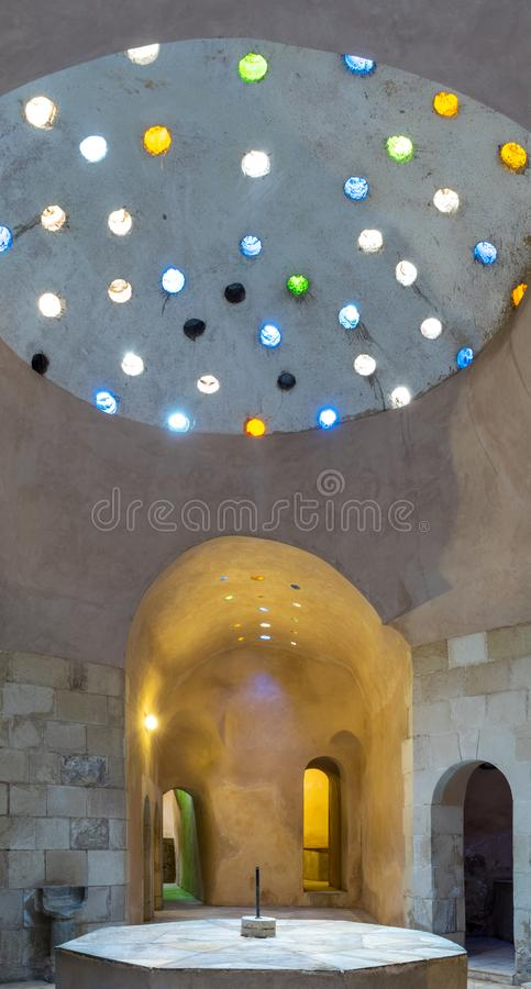 Arched stone wall lighted by glass roof holes at a historical traditional Turkish style public bath. Arched stone wall lighted by colored circular shaped roof royalty free stock image