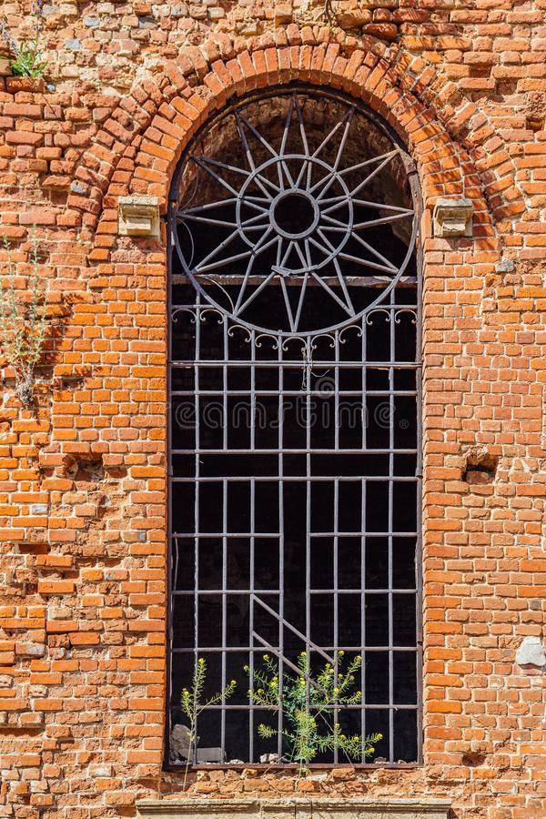 Arched window with bars of old abandoned red brick church stock images