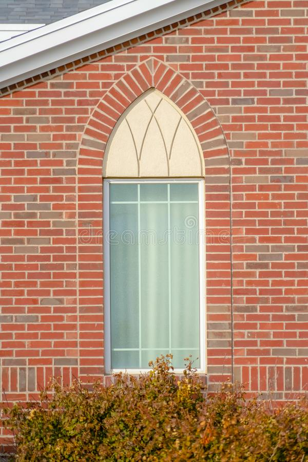 Arched window of a church with red brick wall stock images