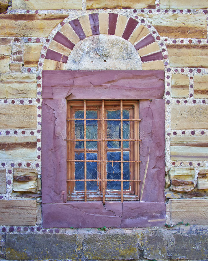 Palladium Stone Around Window : Arched window on red and ocher colored stone wall stock