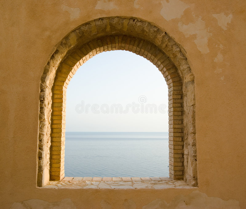 Arched window on the sea. Arched window of bricks on the sea royalty free stock photo