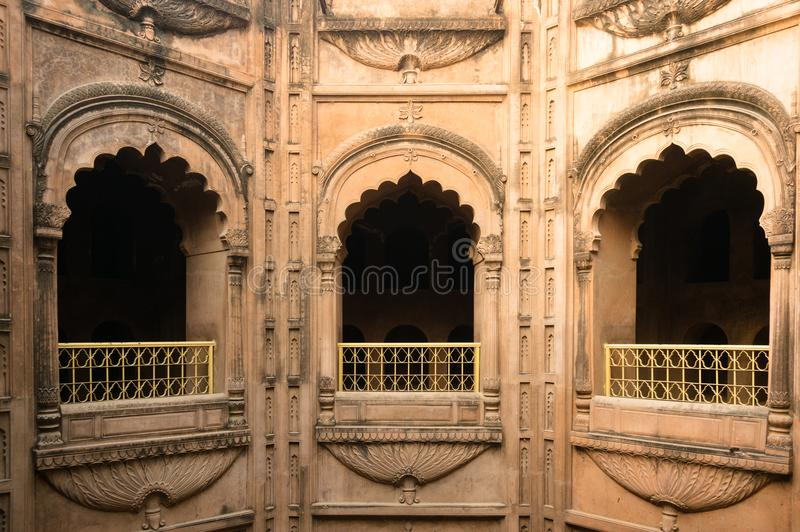 The arched windows at the bouli in bara imambara. Lucknow, India - 3rd feb 2018: The arched sandstone windows of mughal architecture. Shot at the bata imambara royalty free stock images