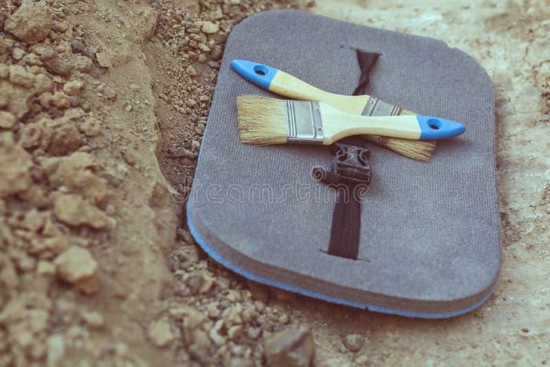 Archeologiczni narzędzia dwa muśnięcia, mata na gruntowym rozdzieleniu na archeologicznych ekskawacjach zdjęcia royalty free