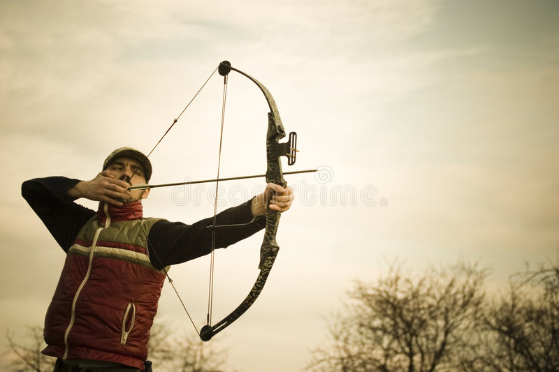 Archer. Man poised to release an arrow from a bow