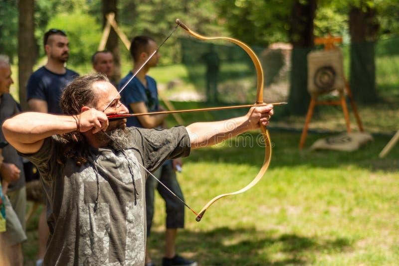 Archer con la freccia del tiro dell'arco nella foresta sul festival e sul torneo del cavaliere fotografia stock libera da diritti