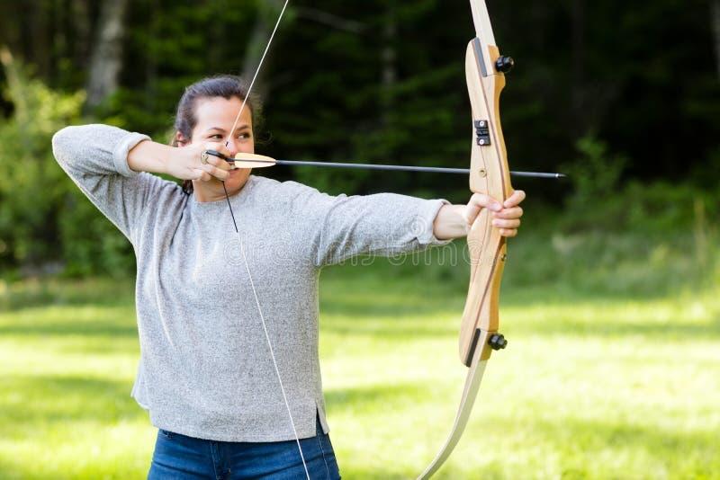 Archer femminile Aiming With Bow e freccia in foresta immagini stock libere da diritti