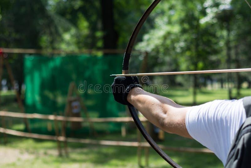 Archer-Hände mit hölzernem Bogentriebpfeil Bogenschießenturnier im Wald lizenzfreies stockbild
