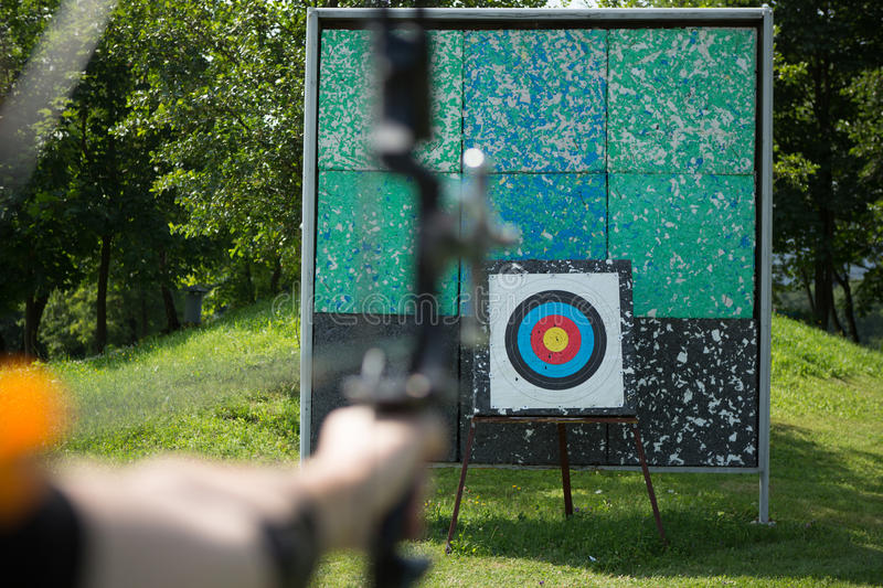 Archer holds his bow aiming at a target stock images