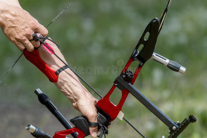 Archer pulls on the sport bow string, taking aim at his target at the competition.  royalty free stock photography
