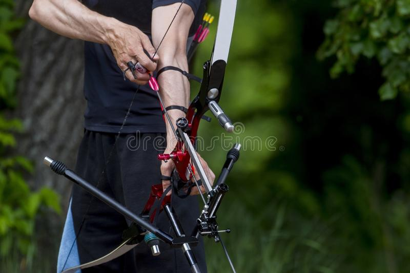 Archer pulls on the sport bow string, taking aim at his target at the competition.  royalty free stock photos