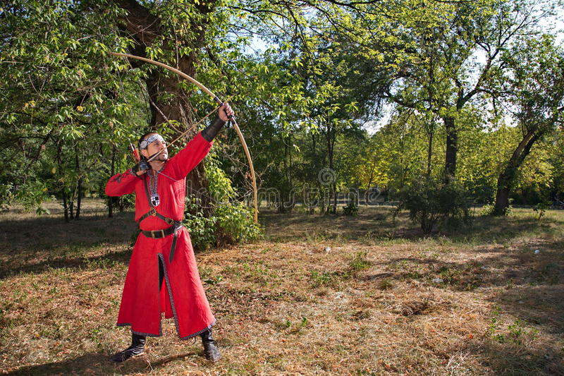 Archer pulls on the string. Man in medieval dress aims a bow royalty free stock image