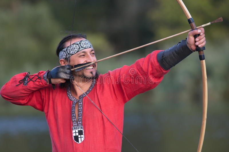 Archer pulls on the string. Man in medieval dress aims a bow royalty free stock photos