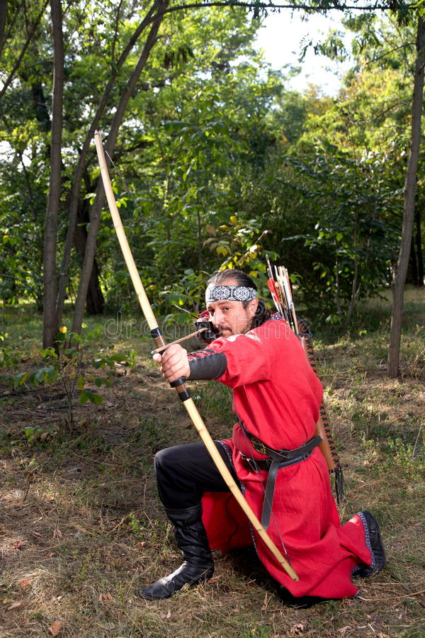 Archer pulls on the string. Man in medieval dress aims a bow royalty free stock images