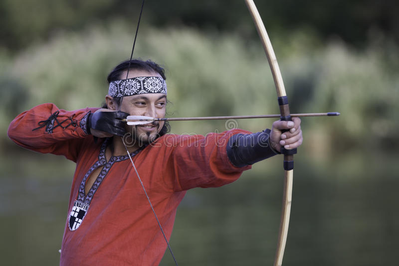 Archer pulls on the string. Man in medieval dress aims a bow stock photo